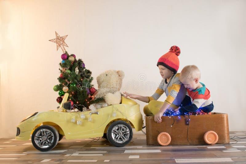 Le petit sourire drôle badine conduire la voiture de jouet avec l'arbre de Noël L'enfant heureux de mode de couleur vêtx apporter photographie stock