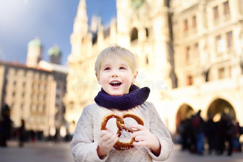 Le petit touriste tenant le pain bavarois traditionnel a appelé le bretzel sur le fond de bâtiment d'hôtel de ville à Munich, All photos stock