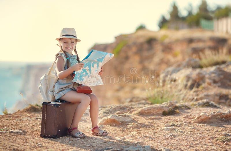 Le petit voyageur étudie la carte tout en se reposant sur la vieille valise photo stock