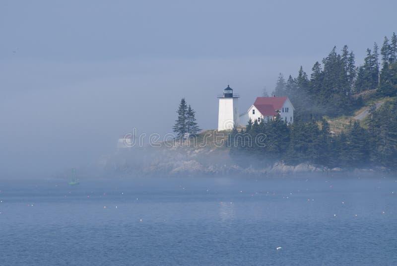 Le phare brumeux d'île dans Maine est Iluminated par le Sun Breaki images libres de droits