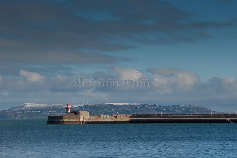 Le phare dans le port brun grisâtre de laoghaire avec la colline de la couverture de Howth par la neige, Irlande photo stock
