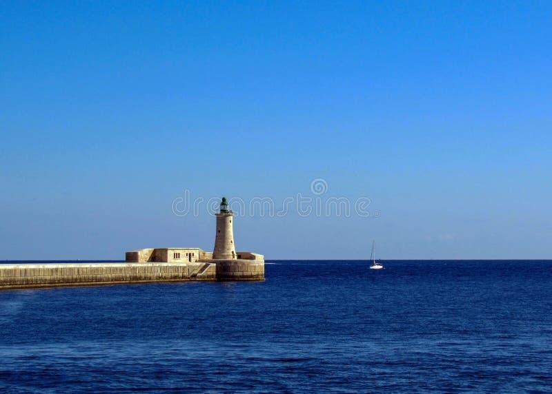 Le phare et le brise-lames de St Elmo du port grand entre la mer bleue et le fond clair de ciel bleu sur l'île méditerranéenne image libre de droits