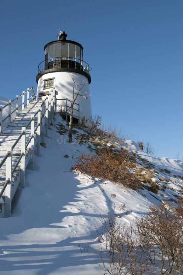 Le phare sur la neige a couvert la falaise photos stock