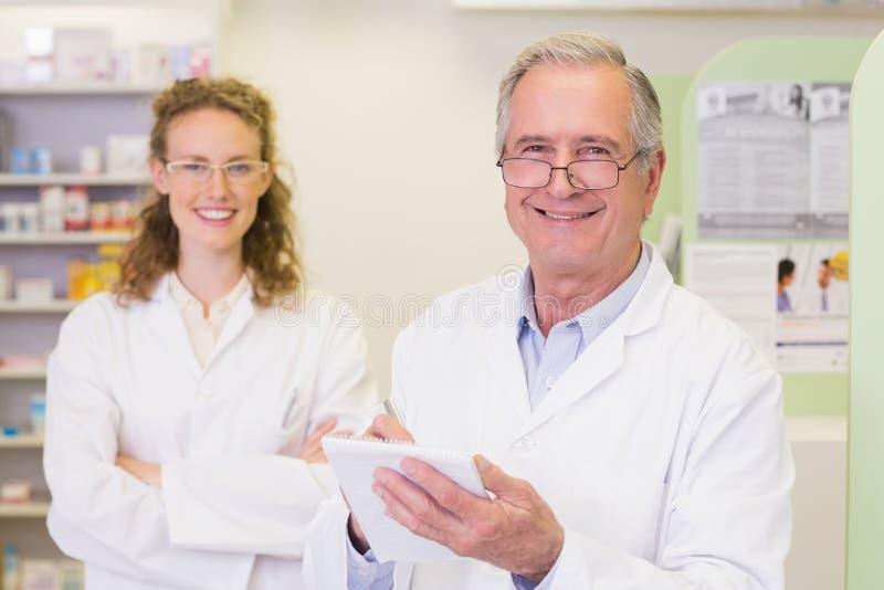 Le pharmacien et son collègue avec des bras ont croisé derrière image libre de droits