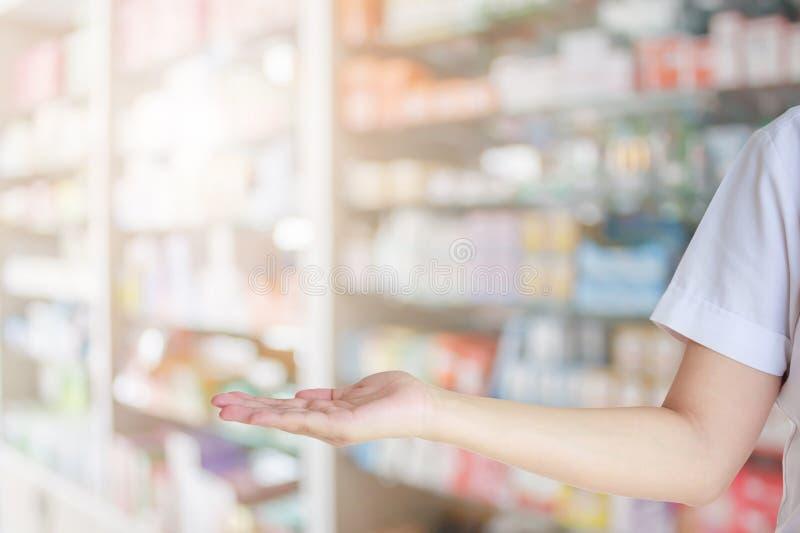 Le pharmacien féminin avec la main ouverte signent plus de le magasin de pharmacie rayonnent images stock
