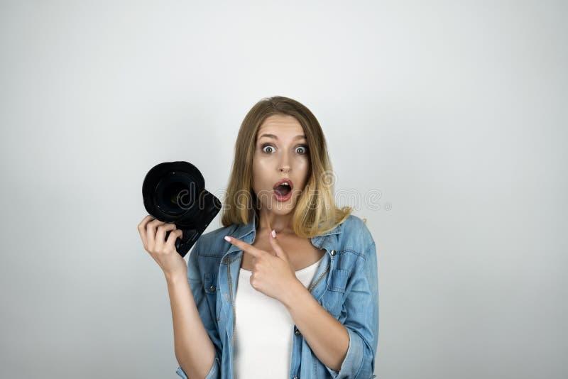 Le photocamera blond heureux de participation de jeune femme dans ses regards de main a étonné le pointage à son fond blanc d'iso images stock