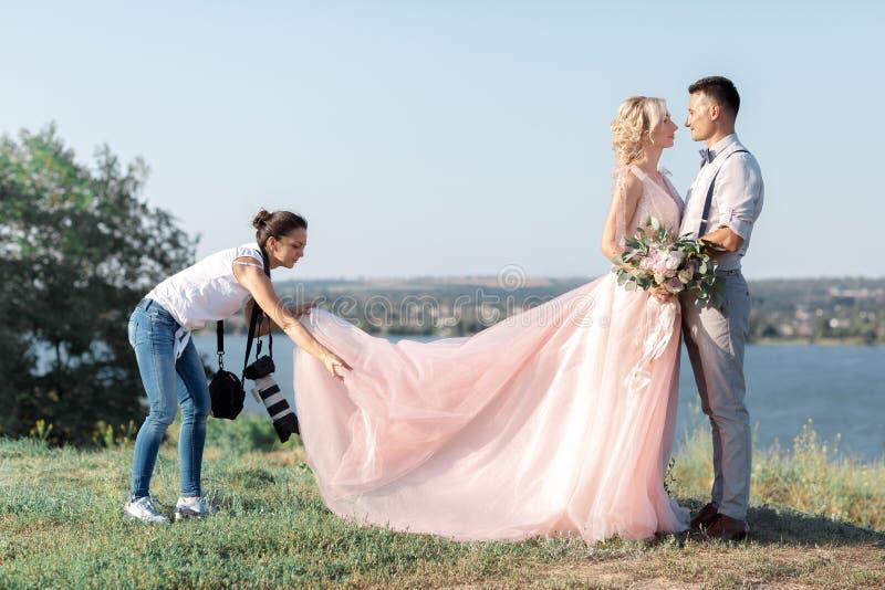Le photographe de mariage prend des photos des jeunes mariés photographie stock libre de droits