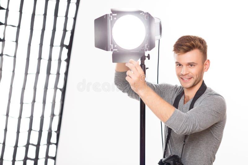 Le photographe de sourire est fixation occupée le projecteur photo libre de droits