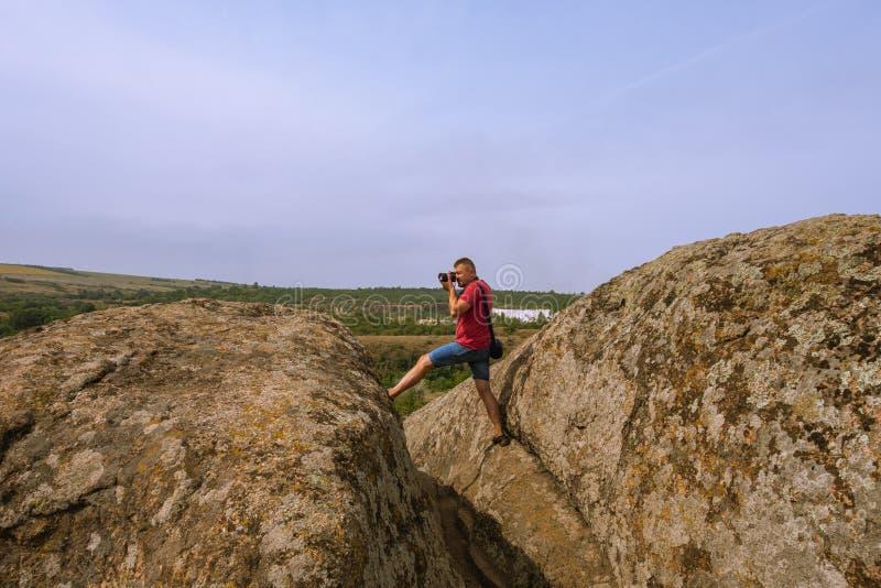 Le photographe prend des photos de nature, se tenant sur une falaise image stock