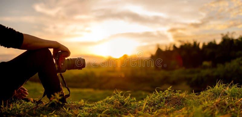 Le photographe s'asseyent pour regarder le coucher du soleil images stock