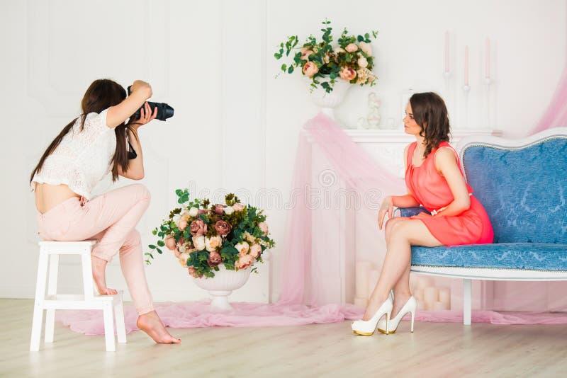 Le photographe sexy prend à des photos le modèle dans le studio photo stock
