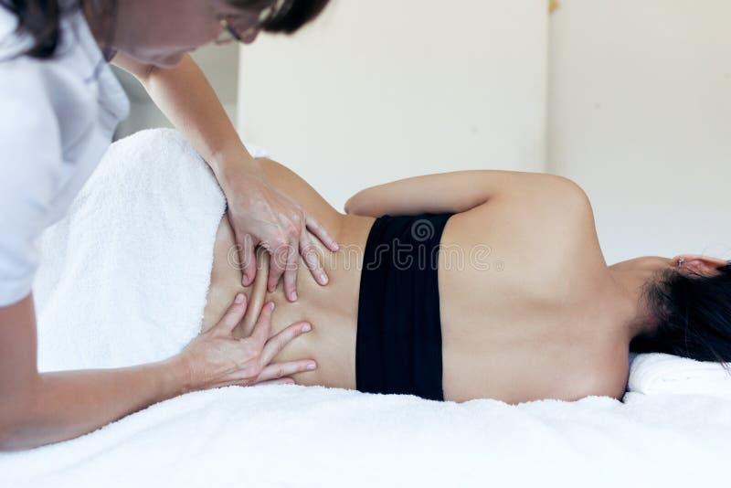 Le physiothérapeute féminin traite des douleurs de dos d'une femme enceinte au centre de station thermale photos stock