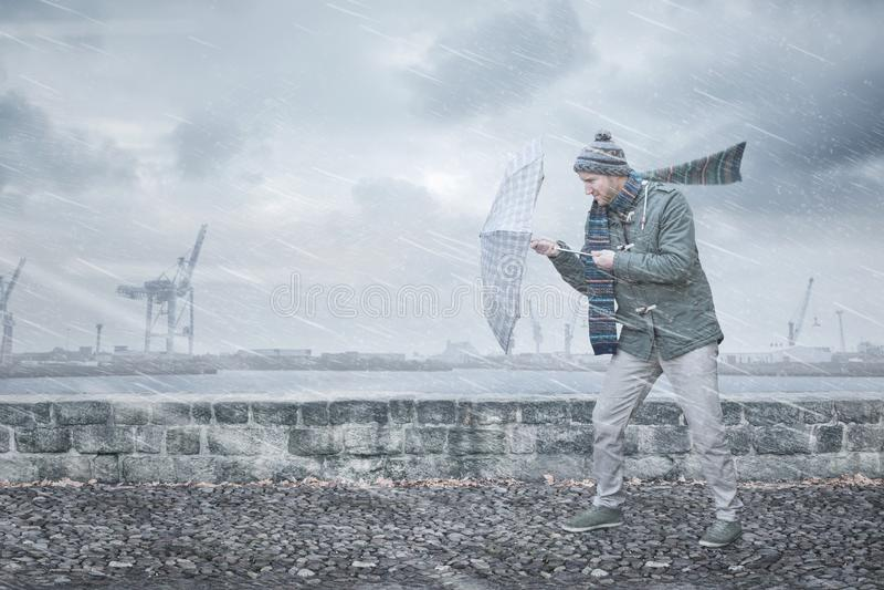 Le piéton avec un parapluie fait face au vent violent et à la pluie image stock