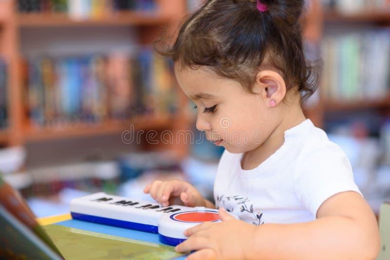 Le pianiste heureux de petite fille d'enfant joue sur un piano de jouet images libres de droits