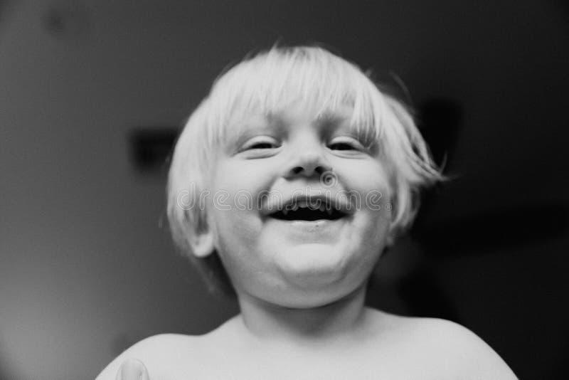 Le piccole espressioni osservate blu dai capelli bionde lunghe sveglie adorabili del fronte del ragazzo del bambino del bambino d fotografia stock