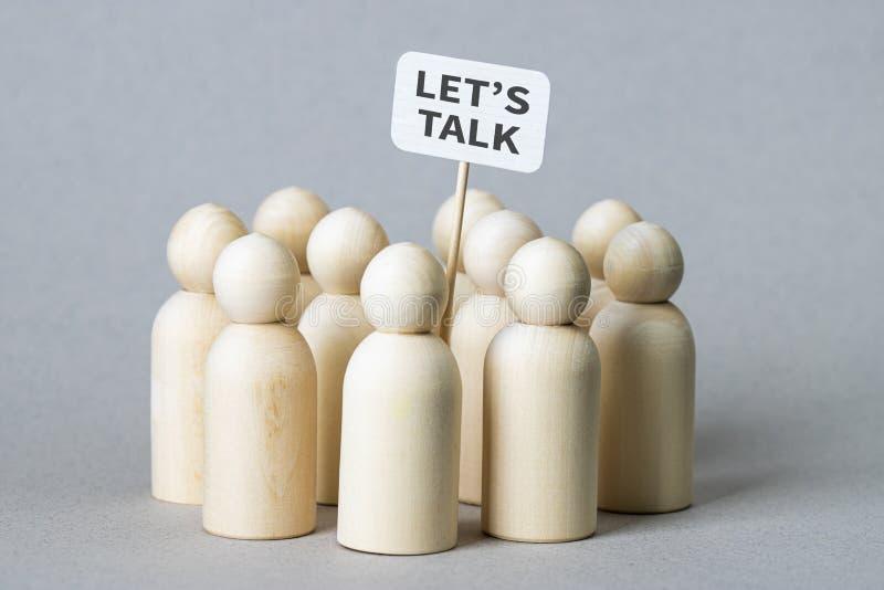 """Le piccole figure di legno con """"ci hanno lasciati parlare """"il manifesto immagine stock"""