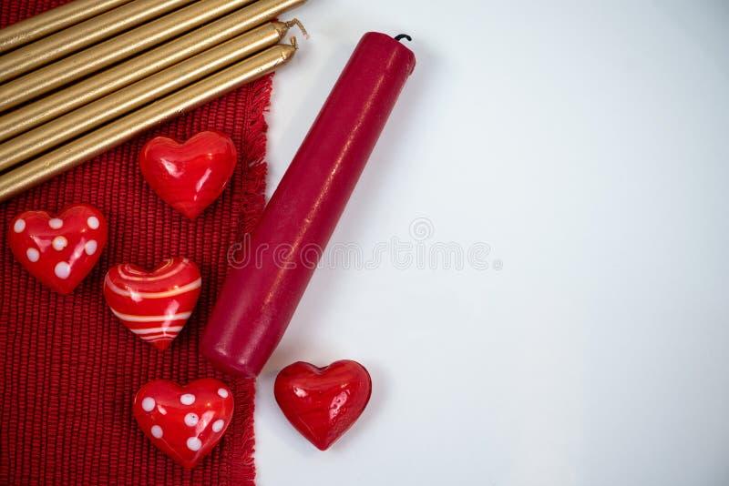Le piccole figurine rosse del cuore fatte di vetro, di rosso e delle candele dell'oro è immagine stock libera da diritti