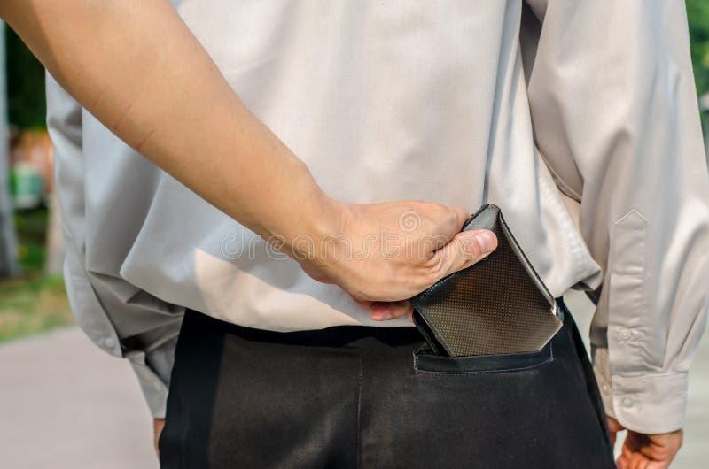 Le pickpocket volant a équipe le portefeuille de la poche arrière image stock