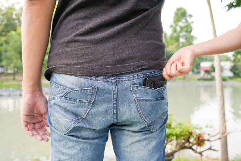 Le pickpocket volant un portefeuille par derrière la poche sur des jeans à les déchirent image stock