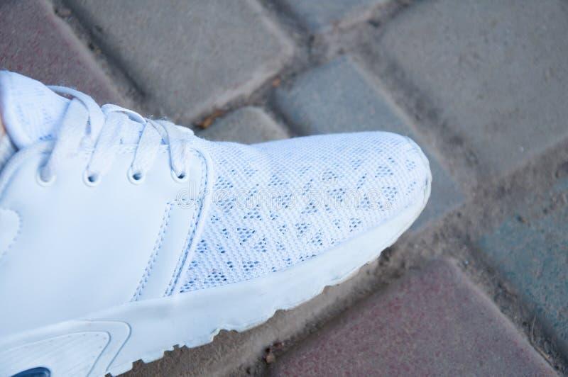 Le pied d'un homme dans les supports blancs d'espadrilles sur les étapes en pierre pendant l'été Marche dans les chaussures photos libres de droits