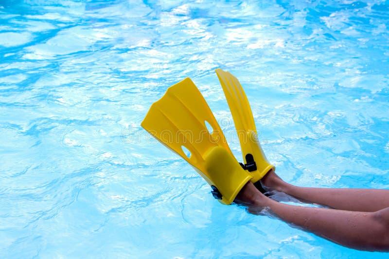 Le pied d'une petite fille portant les nageoires jaunes pour apprennent à nager se reposer au bord de la piscine images stock