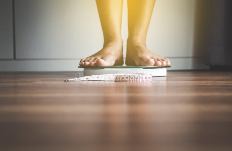 Le pied de femme se tenant dessus pèsent des échelles avec le ruban métrique dans le premier plan images stock