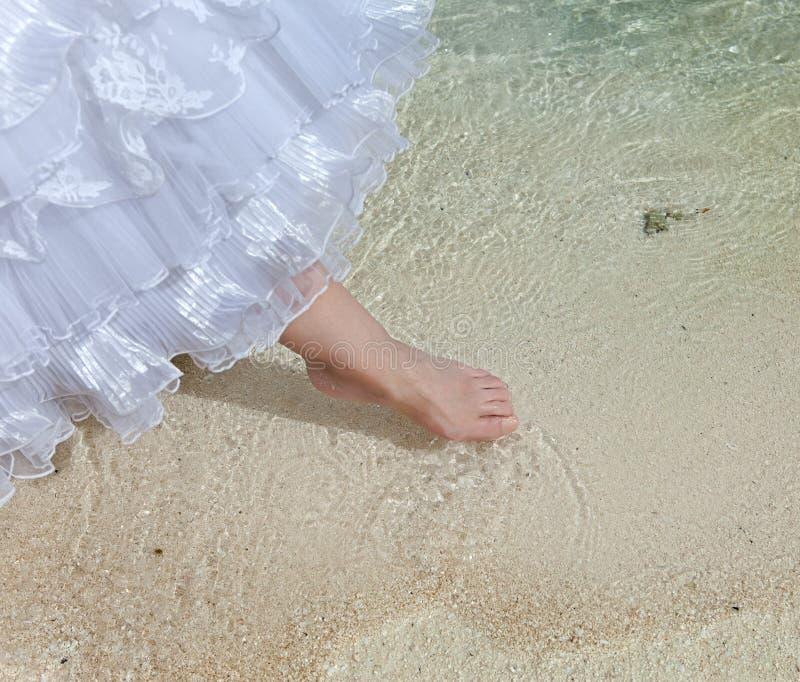 Le pied de la jeune mariée touche l'eau en mer photos libres de droits