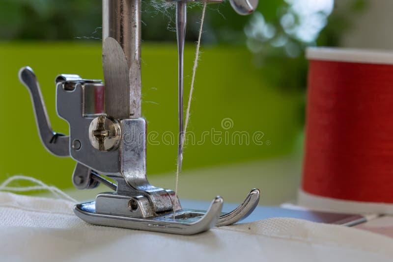 Le pied du ` s de machine à coudre avec une aiguille coud le tissu de couleur d'ecru en gros plan image stock