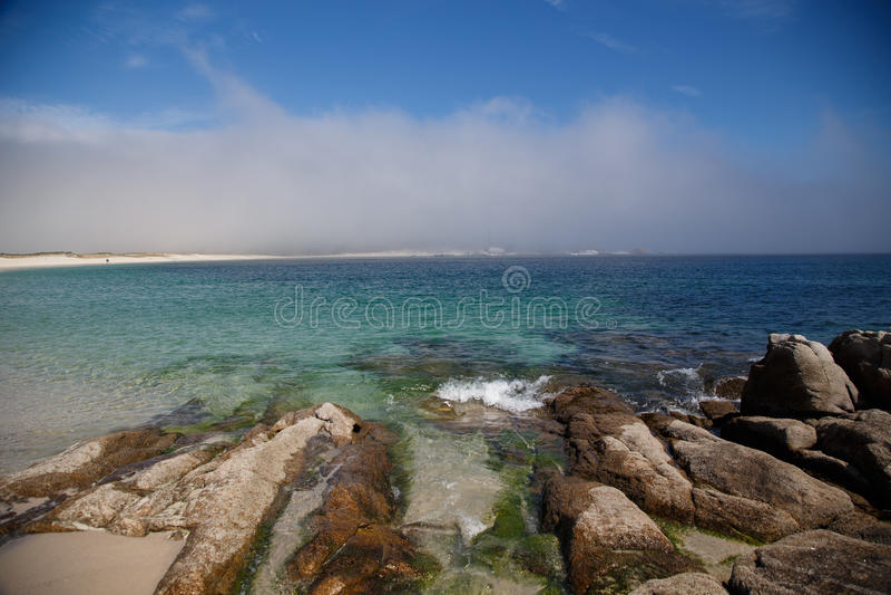 Le pietre alla spiaggia stanno andando all'acqua, isole atlantiche parco nazionale, Spagna immagini stock