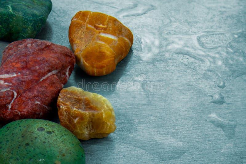 Le pietre colorate si chiudono sull'immagine su superficie con le gocce di acqua Fondo astratto o paesaggio naturale degli elemen fotografie stock