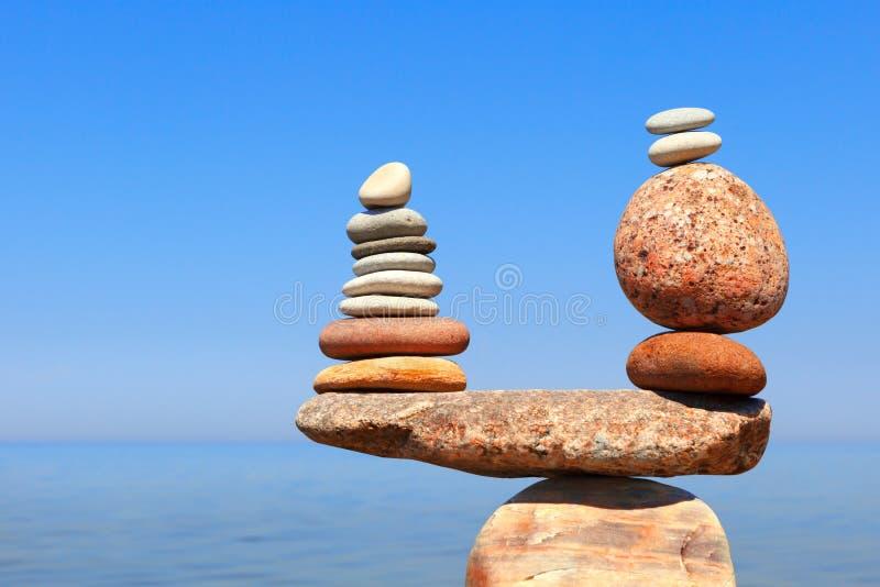 Le pietre equilibrano su un fondo di cielo blu e del mare fotografia stock