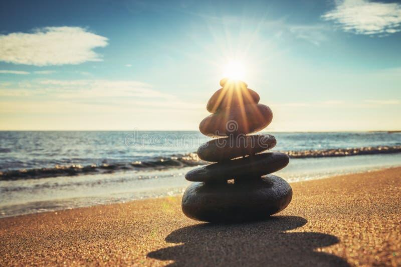 Le pietre equilibrano sulla spiaggia durante l'alba Zen Meditation fotografia stock libera da diritti