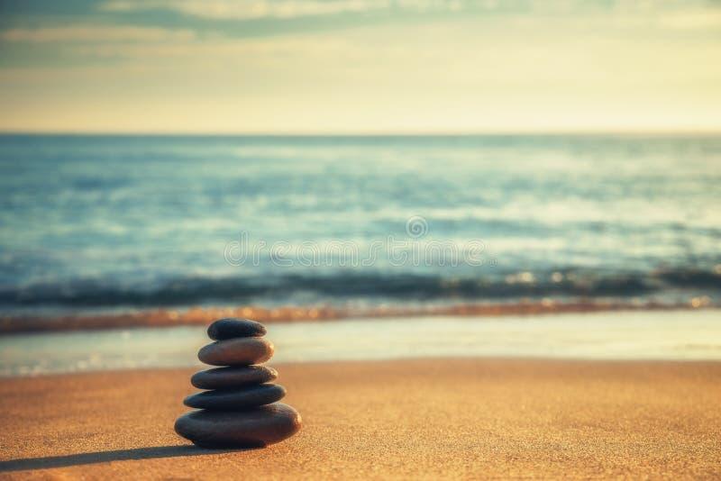 Le pietre equilibrano sulla spiaggia durante l'alba Zen Meditation immagini stock libere da diritti