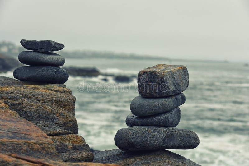 Le pietre hanno piegato in un mucchio sulla costa dell'oceano fotografia stock libera da diritti