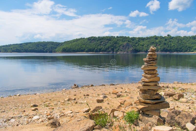 Le pietre impilate si avvicinano al lago immagine stock