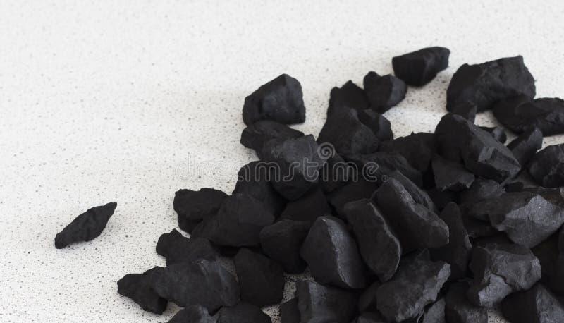Le pietre nere dello shungite si trovano su un fondo bianco, con una copia dello spazio immagini stock libere da diritti
