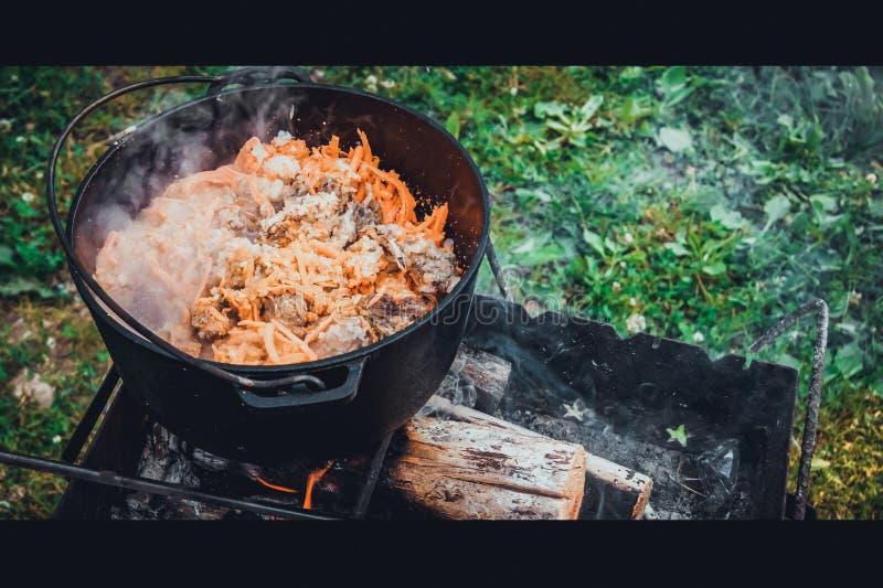 Le pilaf préparent dans un chaudron sur un feu images stock