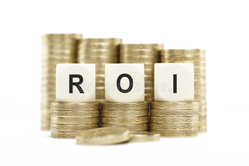 Le pile della moneta di ROI (ritorno su investimento) hanno isolato il fondo bianco immagini stock