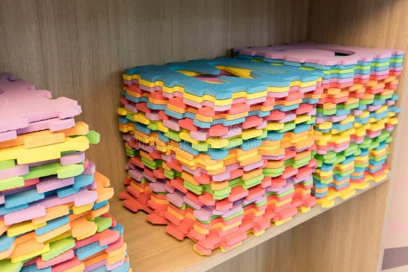 Le pile di stuoie multicolori del puzzle dell'alfabeto hanno sistemato su SH di legno fotografie stock libere da diritti