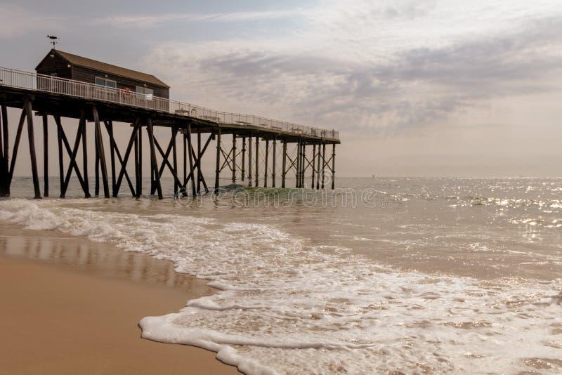 Le pilier de pêche se tient grand comme les vagues coulent doucement vers le rivage un matin ensoleillé photos libres de droits