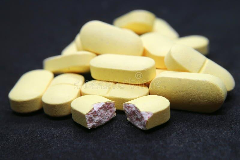 Le pillole accatastano una grande macro foto gialla rotta su fondo nero fotografia stock