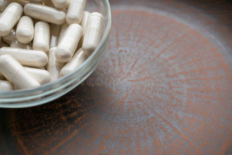 Le pillole delle capsule di bianco della polvere dell'estratto in polvere aglio completano la i fotografia stock libera da diritti