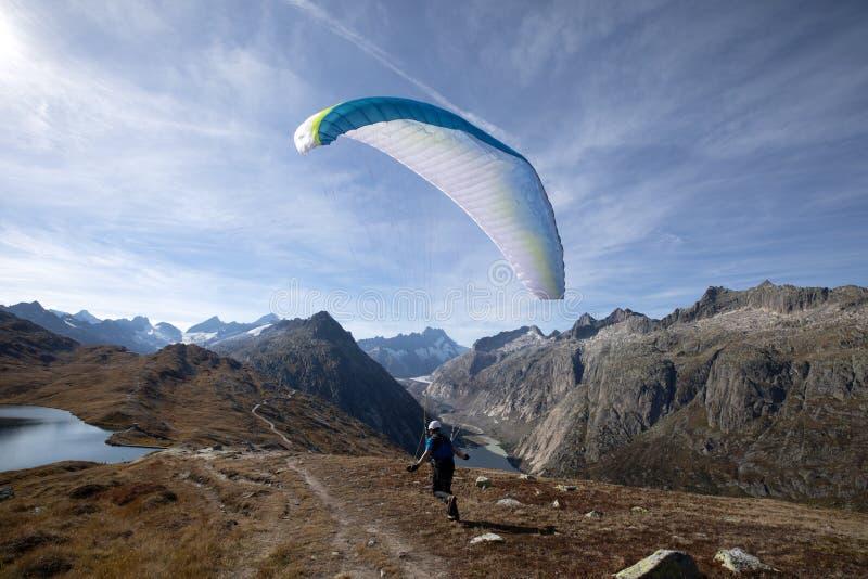 Le pilote de parapentiste décolle avec son parapentiste pour décoller et voler dans la vallée dans les Alpes suisses photos stock