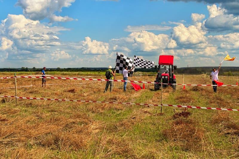 Le pilote sur son tracteur finit Figure la concurrence de pilotage au champ image stock