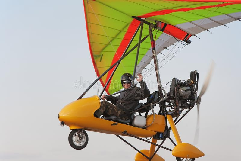 Le pilote vole sur un arrêter-planeur jaune de moteur photographie stock libre de droits