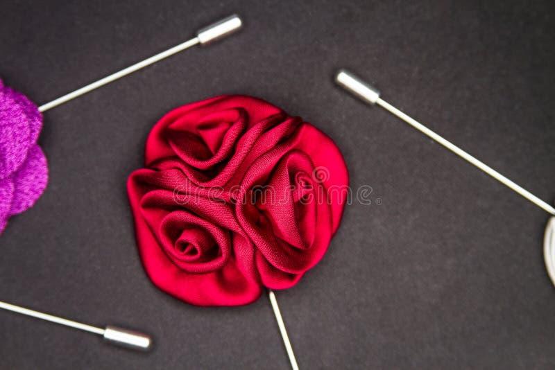 Le Pin rouge de revers du ` s de Rose Men sur le noir a donné à mat une consistance rugueuse d'isolement photographie stock
