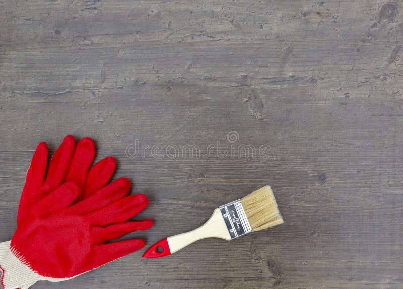 Le pinceau pour des gants de réparation et de travail rouges sur le fond en bois Vue sup?rieure, configuration plate photographie stock