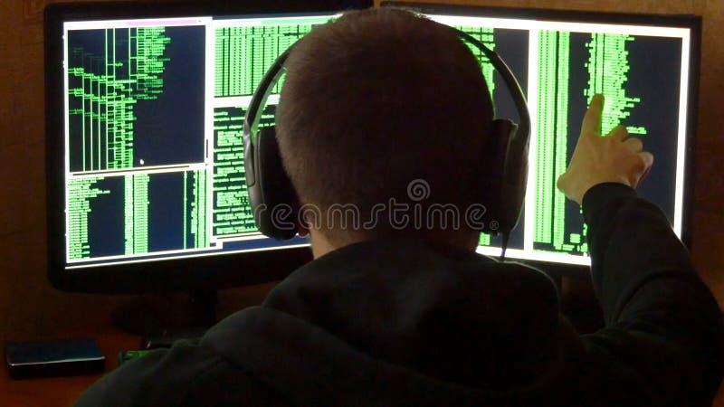 Le pirate informatique est regardé au code binaire Système de réseau pénétrant de pirate informatique criminel de sa pièce sombre images stock