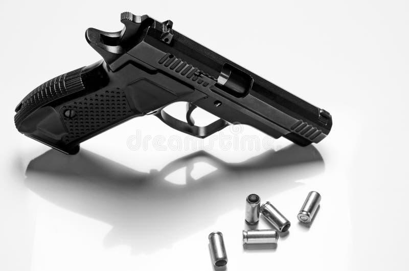 Le pistolet noir en métal se trouve sur un fond blanc, en gros plan image libre de droits