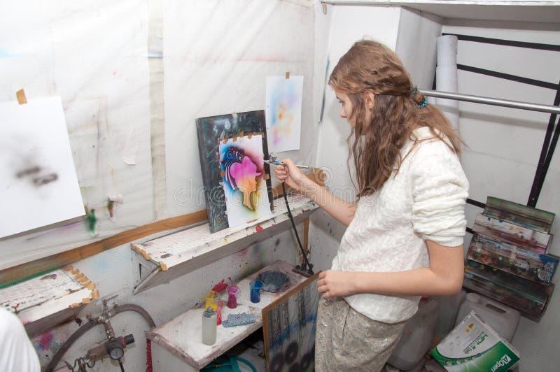 Le pitture dell'adolescente della ragazza con un aerografo hanno colorato brillantemente 24 gennaio 2016 le immagini in uno studi fotografia stock